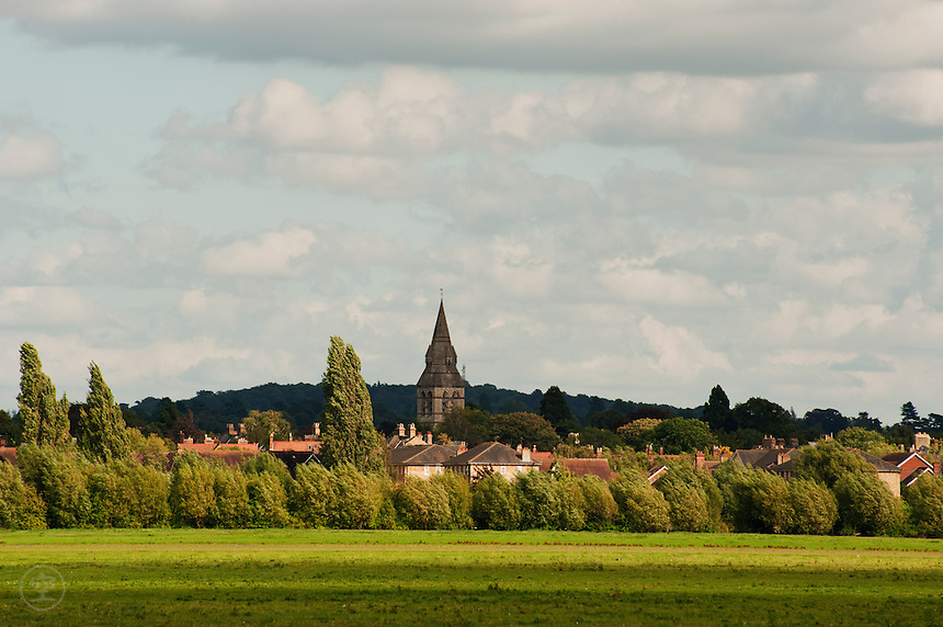 North Oxford seen across Wolvercote Common under a blue sky with clouds.