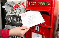 BNPS.co.uk (01202 558833)<br /> Pic: TomWren/BNPS<br /> <br /> A Valentine's Day card is posted at the Lover pop-up post office.<br /> <br /> A British village is cashing in on the cupid effect this Valentine's Day by launching its own postal service so anyone can send a card from the 'world's most romantic village'.<br /> <br /> The tiny village of Lover in Wiltshire has launched the 'Lover Post' with limited edition cards and a special post mark showing it has been sent from the tender-hearted village.<br /> <br /> The quirky gimmick is part of a campaign to save the once-thriving village for the local community.