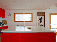 The Poggenpohl kitchen has been designed with a red satinated finish and white Corian worktops