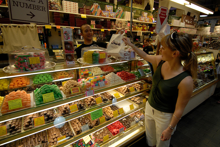 Reading Terminal Market, woman buying candy, mod rel..Philadelphia, Pennsylvania, PA USA.  Photo copyright Lee Foster, 510-549-2202, lee@fostertravel.com, www.fostertravel.com. Photo 236-30561