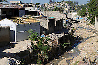 USAID transitional housing built alongside a polluted stream, Port-au-Prince, Haiti. EDV is committed to affecting permanent change in disaster-affected communities worldwide. Their role is to facilitate personal connections between volunteers and the survivors of disasters.  The charity is based on a proven model developed by several landmark organisations that have paved the way for citizens to become disaster volunteers. These landmark organisations have shown that supposedly ordinary people working together with the guidance of knowledgeable leaders can make an extraordinary difference in the lives of those affected by disaster..EDV believe that to provide meaningful relief and reconstruction assistance to disaster affected communities they have to do more than reconstruct buildings. They need to understand and address the factors that made a community vulnerable to the disaster in the first place. The charity's work is organised with these factors in mind so that they can affect change that far outlives their presence..EDV believes that survivor motivation is essential to the recovery of any disaster-affected community. Their operations will always be predicated on the idea that survivors may be traumatised, but they are not helpless. With this in mind, EDV encourages host communities to direct their own recovery. EDV believe that this empowerment is essential in helping survivors feel a renewed sense of control over their lives which will, in turn, help overcome the feelings of hopelessness that can follow a disaster and inhibit long term recovery. EDV also believe that social cohesion is of primary importance in any disaster-affected area. No amount of bricks or mortar will bring about sustainable improvement if communities fail to come together or are disrupted by relief efforts. Therefore, their operations will always aim to foster communication and cooperation within and between the communities they serve.