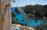 An outdoor shower is mounted on one side of the terrace overlooking the sparkling blue sea