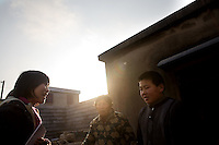 A representative of the Chinese charity the Amity Foundation (left) speaks with the orphan Fan Jian Bo, 11, and his aunt Guo Yu Hua about their situation outside of their home in Fanzhuang Village, Gangyun County, Jiangsu, China.  Fan Jian Bo, 11, was orphaned in 1998, and now lives with his aunt and uncle in Fanzhuang Village, Jiangsu Province, China.  The boy's father died of cancer in 1998, and soon after his mother committed suicide by drinking pesticide.  The boy's uncle has a cerebral embolism and the meager income the family earns from growing cabbages and melons cannot support Fan Jian Bo continuing school.  ..At the time of the picture, China's Amity Foundation charity, was investigating the family's situation in preparation to raise money to financially support these children and other orphans in similar situations.  With Amity's support, each orphan, aged 6-12, would receive approximately 1,400 RMB annually (about 200 USD) to pay for the cost of living. Amity works to keep children out of the institutional orphanages in China, preferring to provide monetary assistance that can help maintain a family environment for the orphans it helps.