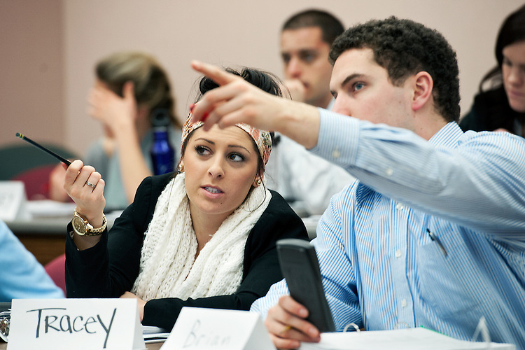 Tracy Hecht (left) and Brian Joyce (right) go over the details of stock analysis during a lecture given by professor of accountancy David Kirch. Photo by: Ross Brinkerhoff.