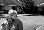 "Bob's wife and daughter embrace after deciding to place Bob in an assisted-living facility, seen behind them. He had become increasingly agitated and had violent spells towards his wife...ltqmb     ""Hard decision"""