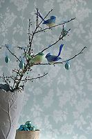 Bird decorations and small foil covered chocolate Easter eggs hanging from cherry blossom in a vase makes a pretty and unique Easter display