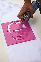Moscow Russia, 23/07/2011..A young woman spray-paints an image of Prime Minister Vladimir Putin on her shirt as members of Putin's Army, a group of Pro-Putin activists that launched on the Internet last week with a video of scantily clad young Russian women, campaign in central Moscow under the slogan &quot;Tear Something For Putin&quot;.