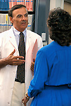 doctor talking to receptionist in medical records section of his office