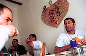 Asylum seekers who had stayed in Sangatte, France, eat breakfast at their new temporary home in Dover, England. They had stayed at the Red Cross refugee camp near Calais and smuggled themselves acrossed the English Channel...Picture taken April 2002 in Sangatte by Justin Jin. Copyright 2002 by Justin Jin.