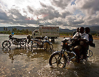 A moto taxi crosses the Riviere de la Cosse in Jacmel as others use the water to wash their vehicles. Locals say when the rains come, the river will be impassable. January's earthquake killed hundreds of thousands of people and caused significant and lasting structural and economic damage in the Caribbean nation.
