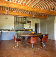 A spacious kitchen dining room with a heavy beamed ceiling and tiled floor. Modern, contemporary furniture contrasts with the original, rustic features of the room.