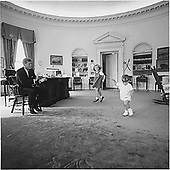 The Kennedy children, Caroline Kennedy and John F. Kennedy,Jr., visit their Dad, United States President John F. Kennedy in the Oval Office of the White House in Washington, DC on October 10, 1962. <br /> Credit: White House via CNP