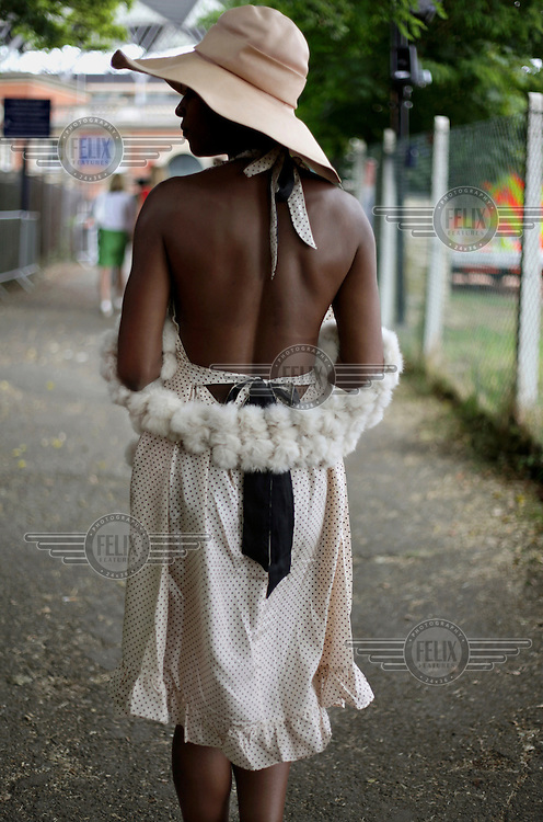 A woman wearing a backless dress with a fur stole arrives at the railway station for the Royal Ascot race meeting. The annual event, during which each day begins with the Queen's arrival in a horse drawn carriage, dates back to 1711 when Queen Anne organised the first races on what was then a heath near Windsor Castle.