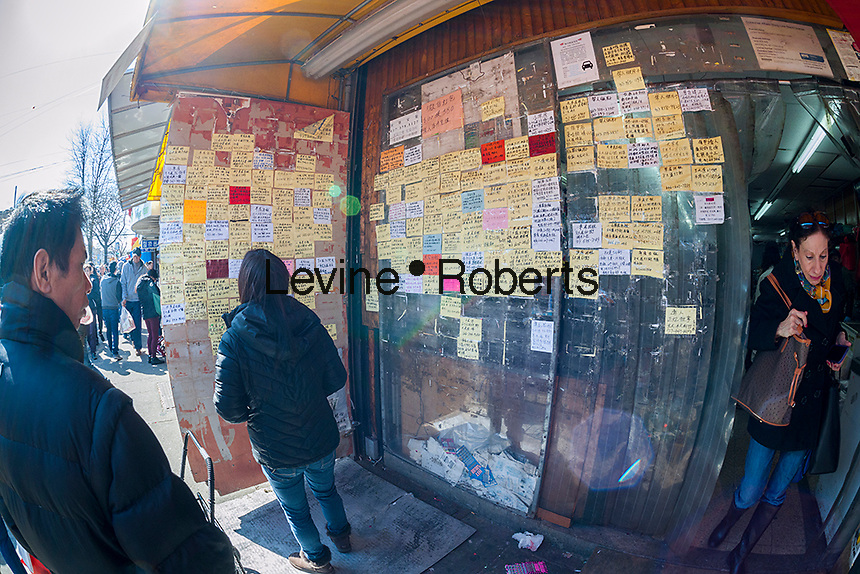 Cards posted showing employment opportunities posed in front of a grocery on Eighth Avenue in the Sunset Park neighborhood in Brooklyn in New York on Sunday, February 28, 2016 during the Lantern Festival street fair. Sunset Park has become Brooklyn's Chinatown as Chinese and other Asian groups have moved there and businesses have sprouted up to cater to them. (© Richard B. Levine)