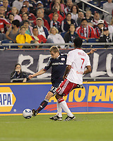 New England Revolution forward Zak Boggs (33) plants his foot for a cross as New York Red Bulls defender Roy Miller (7) defends. The New England Revolution defeated the New York Red Bulls, 3-2, at Gillette Stadium on May 29, 2010.