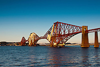 A (close to) sunset photo of the Forth Rail Bridge, crossing the Firth of Forth between Edinburgh and Fife. Snow can be seen on the mountains in Fife, across the Forth..The Forth Bridge is an instantly recognisable landmark associated with Scotland and Edinburgh in particular and might be nominated as one of the UNESCO World Heritage Sites in Scotland.
