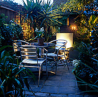 This small urban garden is teeming with plants and has a tiled patio for summer dining