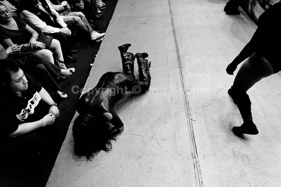 """A female Lucha libre wrestler lies on the floor outside the ring after being knocked down during a fight at Arena Mexico in Mexico City, Mexico, 26 April 2011. Lucha libre, literally """"free fight"""" in Spanish, is a unique Mexican sporting event and cultural phenomenon. Based on aerial acrobatics, rapid holds and the use of mysterious masks, Lucha libre features the wrestlers as fictional characters (Good vs. Evil). Women wrestlers, known as luchadoras, often wear bright shiny leotards, black pantyhose or other provocative costumes. Given the popularity of Lucha libre in Mexico, many wrestlers have reached the cult status, showing up in movies or TV shows. However, almost all female fighters are amateur part-time wrestlers or housewives. Passing through the dirty remote areas in the peripheries, listening to the obscene screams from the mainly male audience, these no-name luchadoras fight straight on the street and charge about 10 US dollars for a show. Still, most of the young luchadoras train hard and wrestle virtually anywhere dreaming to escape from the poverty and to become a star worshipped by the modern Mexican society."""