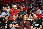 Spectators filming with their digital equipment whilst watching the MMA cage fighting<br />