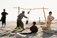Afghan boys collecting water from a desert well. The water will be carried back to the boys' families in old inner-tubes. <br /> <br /> Western Afghanistan