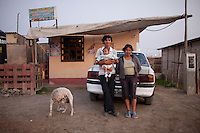 A couple poses for a portrait with their child on Thursday, Apr. 16, 2009 in Ventanilla, Peru.