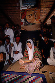 Larkana, Pakistan<br /> November 16, 1988<br /> <br /> Benazir Bhutto visits the grave of her father near Larkana. Benazir is the eldest child of former Pakistan President and Prime Minister Zulfikar Ali Bhutto. <br /> <br /> She was placed under house arrest in the wake of her father's imprisonment and subsequent execution in 1979. In 1984 she became the leader in exile of the Pakistan Peoples Party (PPP), her father's party, though she was unable to make her political presence felt in Pakistan until after the death of General Muhammad Zia-ul-Haq. <br /> <br /> On 16 November 1988 Benazir's PPP won the largest bloc of seats in the National Assembly. Bhutto was sworn in as Prime Minister in December, at age 35 she became the first woman to head the government of a Muslim-majority state in modern times. <br /> <br /> She was removed from office 20 months later under orders of then-president Ghulam Ishaq Khan for alleged corruption. Bhutto was re-elected in 1993 but was again removed by President Farooq Leghari in 1996, on similar charges. Bhutto went into self-imposed exile in Dubai in 1998, until she returned to Pakistan on October 2007, after General Musharraf granted her amnesty and all corruption charges withdrawn.