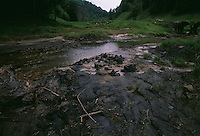 Water from a once clear stream flows over sludge. A thunderstorm in the fall of 2000, more than 260 billion gallons of sludge poured out of a mountain surrounding people's homes, contaminating the drinking water in 17 communities.