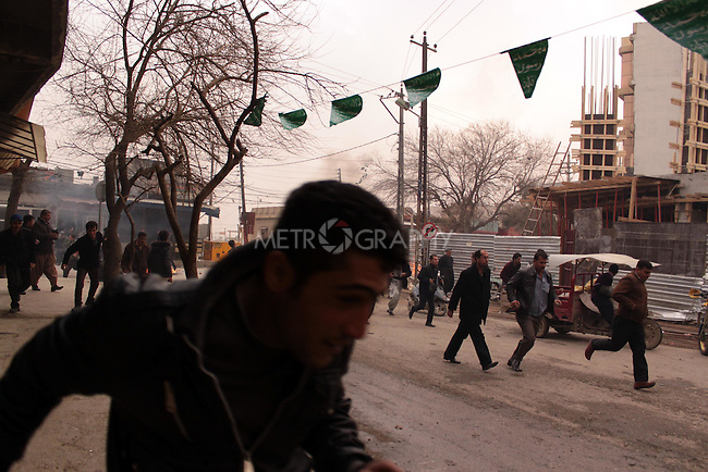 SULAIMANIYAH, IRAQ: Protesters duck for cover as the police chase them through the streets...A third day of violence rocks the Iraqi Kurdish city of Sulaimaniyah.  Tensions between protesters and security forces flare after the security forces continue to use life ammunition during the demonstrations...Photo by Aram Karim