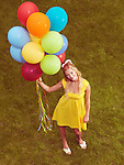 Young smiling woman standing on grass with a bunch of colorful helium balloons in her hand. Retro stylized image.