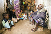 Somaliland. Waqohi Galbed province. Hargeisa. Yusuf Qawdhan Qalib is a black muslim man and a Tubeculosis (TB) patient. He sits, during a short home visit, with his wife and children on the flloor of his traditional somali hut. The Global Fund through the ngo ( Non-governmental organization ) World Vision supports the programm with a Tuberculosis grant (financial aid). Somaliland is an unrecognized de facto sovereign state located in the Horn of Africa. Hargeisa is the capital of Somaliland. © 2006 Didier Ruef