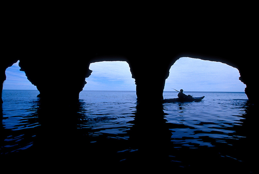 A sea kayaker expores sea caves on Devils Island in the Apostle Islands National Lakeshore near Bayfield, Wis.