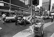 May, 1980. Manhattan, New York City, NY. A pretzel vendor on a frantic Times Square street corner. Traffic is heavy and chaotic.<br /> <br /> Manhattan, New York City, NY. Mai, 1980. Times square &agrave; la 43eme rue. Le trafic est intense 24 heures sur 24 et les encombrements sont incessants. Un marchant de bretzels encombre le trottoir.