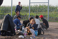 Police officers detain illegal migrants after crossing the razor wire fence on the border between Serbia and Hungary near Roszke (about 174 km South of capital city Budapest), Hungary on September 15, 2015. ATTILA VOLGYI