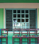 Chairs on porch with green wall and window