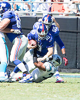 The Carolina Panthers played the New York Giants at Bank of America Stadium in Charlotte, NC.  The Panthers won 38-0 for their first victory of the season.  The Giants dropped to 0-3.  New York Giants quarterback Eli Manning (10) is sacked by Carolina Panthers defensive end Greg Hardy (76)