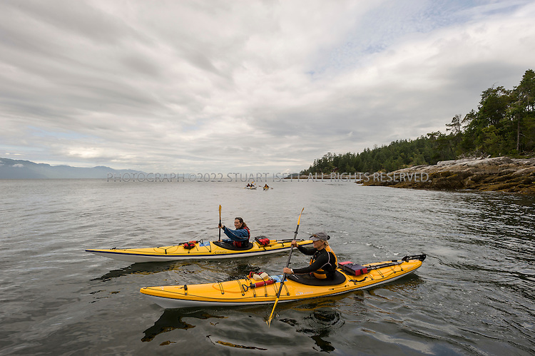7/4/2008--Halfmoon Bay, British Columbia, Canada..Ruth Kjorven (front) and Chelsea Rubin (behind) kayak near Secret Cove. Guests from the Rock Water Secret Cover Resort can rent kayaks from Halfmoon Sea Kayaks on the beach at the resort. ..The rocky Sunshine Coast of British Columbia is just two hours northwest of Vancouver and can only be reached by ferry from Horseshoe Bay near Vancouver. Much of the coastline is accessible by boat only and protected as provincial parkland and visitors have an array of activities to choose from including hiking, kayaking, diving and sailing. Hotels, resorts and B&Bs offer a range of accommodation for travelers...©2008 Stuart Isett. All rights reserved.