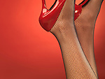 Young woman wearing black fishnet stockings and red sexy high heel shoes