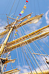 Looking up at ships mast with rigging, lines, yardarms, flags and blue sky