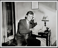 BNPS.co.uk (01202 558833)<br /> Pic: RRAuction/BNPS<br /> <br /> Kennedy in his Beacon Hill apartment on 112 Bowdoin St., Boston, speaking on the telephone and showing off a handful of telegrams.<br /> <br /> Incredibly-rare photos highlighting the first foray into politics for John F. Kennedy that would eventually cost him his life have come to light.<br /> <br /> The 100 black and white snaps show a youthful-looking JFK from 1946, when he was campaigning to become a US congressman for the first time.<br /> <br /> The tragic future president is seen during an oration lesson where he was given help by an expert with public speaking and posture.<br /> <br /> The 29-year-old is also depicted mingling with the public at an annual parade and as well as celebrating his first political victory - a congressional primary vote - in June 1946.<br /> <br /> The images are being sold by US-based RR Auction.