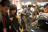 Customers shop at the grand opening of the Uniqlo Flagship store on Fifth Avenue in New York on Friday, October 14, 2011.  The store is a staggering 89,000 square feet on multiple levels and is Fast Retailing's second store in the United States with a third opening next week in the Herald Square shopping district. The largest store on Fifth Avenue filled to the brim with affordable clothing it competes with stalwarts such as the Gap and Zara which are in the immediate proximity. Fast Retailing plans on opening 200 to 300 stores worldwide until 2020 and currently has 1000 stores. (© Richard B. Levine)