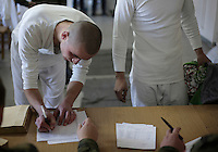A new conscript signing papers as he leaves his belongings on deposit. This year's class of drafted recruits is the final one after 90 years of compulsory military service, as Poland's army turns professional in 2009.