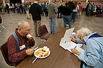 Election 2012- A tale of two elders: Election volunteer Ray Pearson chows down lunch, while across the table a voter lasers in on her choices. Turnout was high this day, with long lines to register and then vote, with waits of three hours or so.