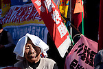 An older woman union activist lshields herself from the sun as she istens at The National Worker`s Rally organised by Marxist groups and Doro Chiba labour union in Hibiya Park, Tokyo, Japan, Sunday, November 1st 2009