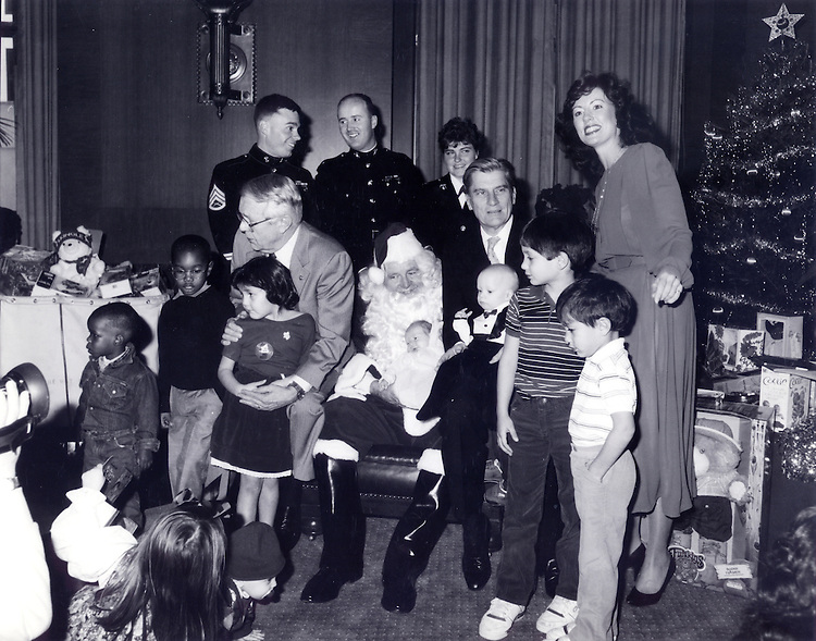 """It was taken in December 1987 at a U.S. Marine Corps Reserve """"Toys for Tots"""" event in the Rules Committee hearing room.  The seated Senators from left are Sens. Wendell Ford, Howell Heflin, and John Warner. Senator Warner is holding Austin Caldwell, age 6 months, son of the woman standing, Robin Caldwell, who is still on Senator Warner's staff.."""