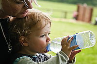 Young boy drinking water from a bottle, sitting on his mother's lap.