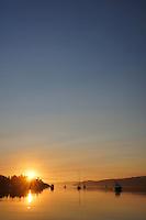 Sunrise over boaters at achor in Lopez Sound just off Spencer Spit, Spencer Spit State Park, Washington, USA