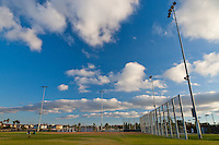 The baseball field at Stanton Central Park on a day with gorgeous puffy white clouds in a blue sky.  A super-wide-angle lens makes the lights look like they soar above the field.