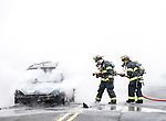 MANASQUAN, NJ — April 1, 2016 —Manasquan firefighters Kevin McCredie and Tom Schofield knock down flames from a 2000 Ford Focus that was fully engulfed at about 9:40am on Broad Street, here. The driver of the vehicle was not injured.  photo by Andrew Mills