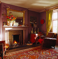 A well worn leather armchair stands in the corner of the aubergine coloured sitting room