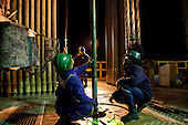 BAGHDAD, IRAQ: Workers at the drilling tower of well number 7 at the Midland Oil Company field.